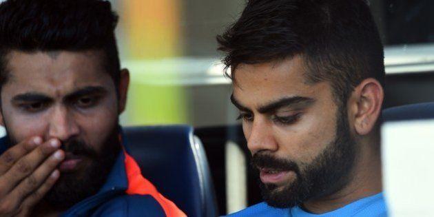India's Virat Kohli (R) and Ravindra Jadeja (L) relax after completing a final training session ahead...