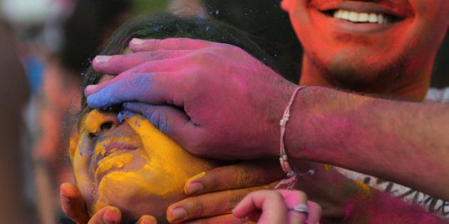 Participants place colored powder on a woman's face as they join celebrations of the Holi festival in...