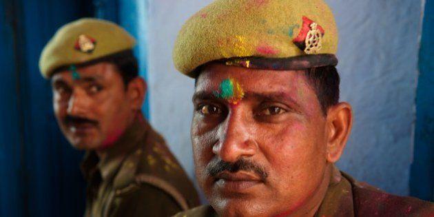 BARSANA, UTTAR PRADESH, INDIA - 2013/03/21: Even policemen can't quite escape the colours of Holi. Revellers...
