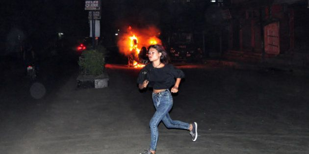 In this Thursday, March 5, 2015 photo, an unidentified girl runs in front of a car set on fire by a mob,...