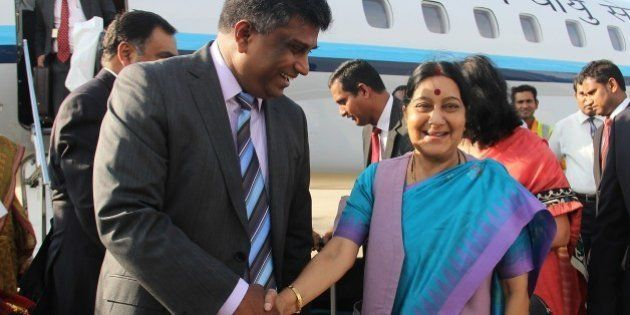 Indian Foreign Minister Sushma Swaraj (R) shakes hands with Sri Lankan Deputy Foreign Minister Ajith...