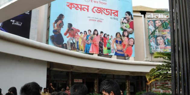 Bangladeshi men look at a billboard advertising the film 'Common Gender' at a movie theatre in Dhaka...