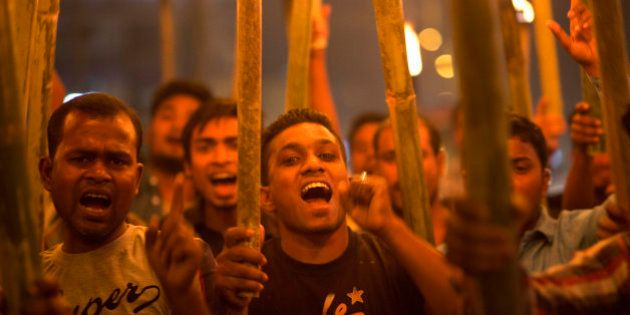 Activists of All Assam Minorities Students Union shout slogans during a torch protest against the lynching...