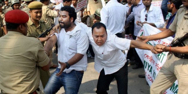 Indian policemen detain activists of Asomiya Yuva Mancha (AYM) during a protest against the lynching...