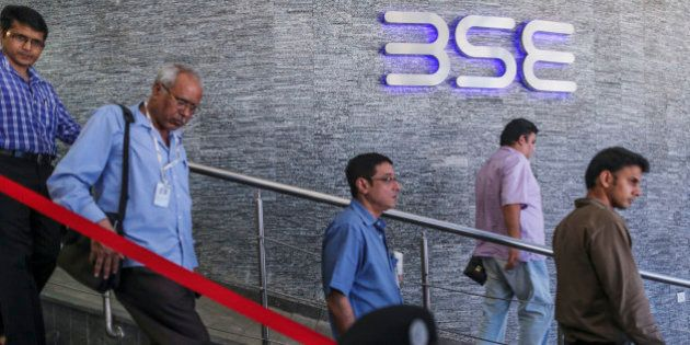 People walk past the Bombay Stock Exchange (BSE) logo displayed outside the building's lobby in Mumbai,...