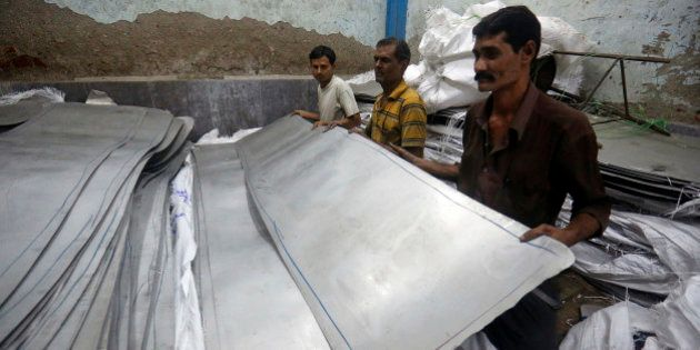Workers pick up a sheet of stainless steel inside a manufacturing workshop in the suburb of Mira-Bhayander...