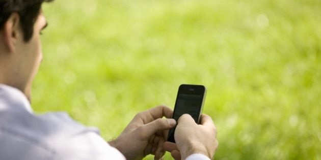 A businessman sitting on the grass, using his mobile