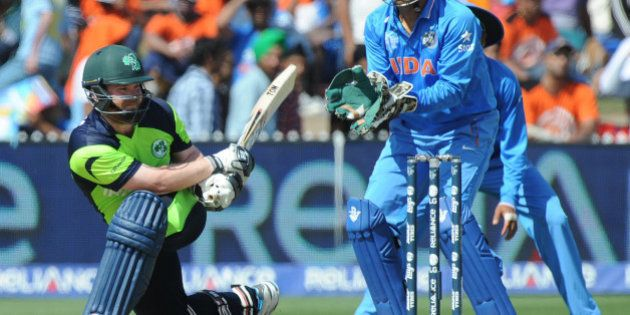 Ireland's Paul Stirling plays a sweep shot as India's wicketkeeper MS Dhoni watches during their Cricket...