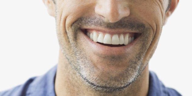 Close-up portrait of smiling man against white