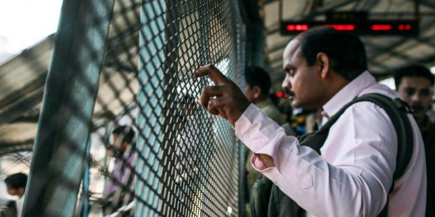 A man looks out from behind a fence on a footbridge at Kurla railway station in Mumbai, India, on Saturday,...