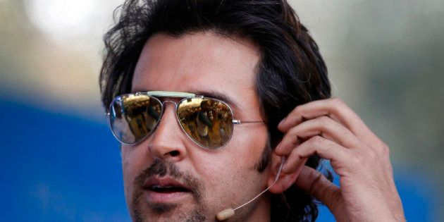 Bollywood actor Hrithik Roshan adjusts his microphone as he interacts with his fans during an event to...