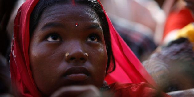 A tribal woman whose land is being acquired by government participates in a protest with others against...