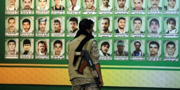 A Huthi militiaman looks at a wall bearing the portraits of 'martyrs', who were reportedly killed during...