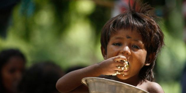 An Indian homeless child eats rice on a roadside in Allahabad, India, Friday, July 5, 2013. The Indian...