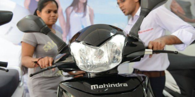 A picture taken on October 8, 2014 shows a woman (L) looking at the recently launched Mahindra Gusto...
