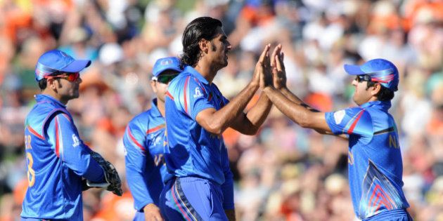Afghanistan bowler Shapoor Zadran, centre, is congratulated by teammates after dismissing New Zealand's...