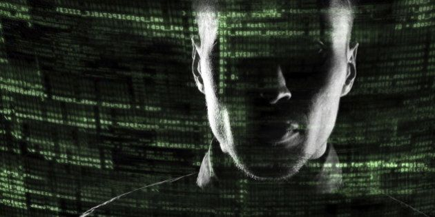 Silhouette of a hacker isolated on black with binary codes on