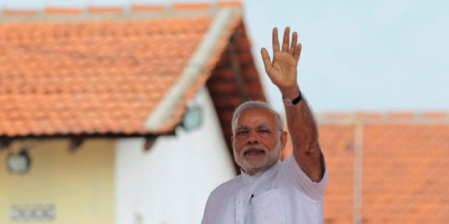 Indian Prime Minister Narendra Modi waves to the gathering during the handing over of homes under a housing...