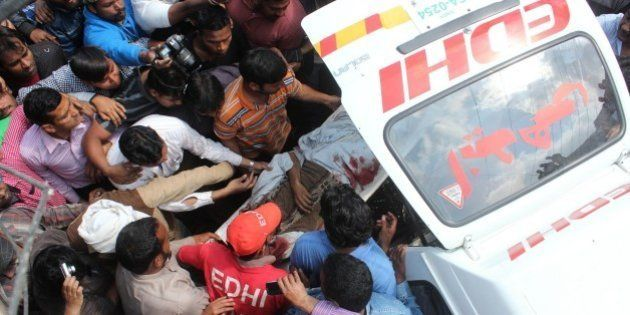 LAHORE, PAKISTAN - MARCH 15: Pakistani rescue worker and people carry the body of bomb blast victim in...