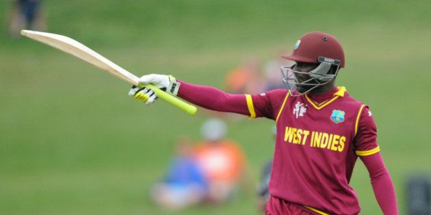 West Indies batsman Jonathan Carter waves his bat to the crowd after reaching 50 runs during their Cricket...