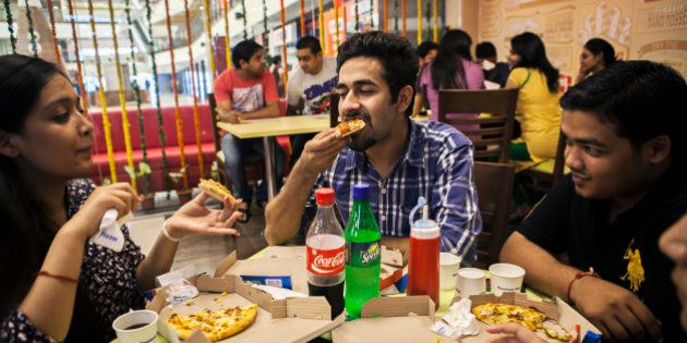 Customers eat at a Domino's Pizza outlet, operated by Jubilant Foodworks Ltd., after the opening of the...