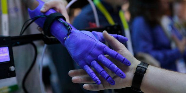 An attendee shakes hands with a 3D-printed robotic prosthetic arm created based on an image scanned with...