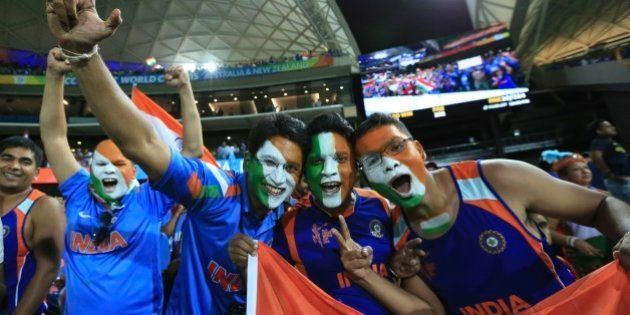 Indian cricket fans, face painted with colors of the Indian flag react to the camera after India won...