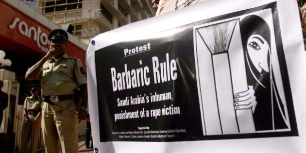 An Indian human rights activist holds banner as she protests against the punishment of a Saudi Arabian...