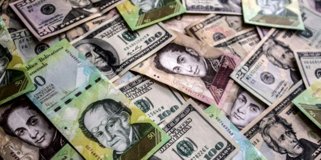 Venezuelan bolivar notes and various denominations of U.S dollar bills are arranged for a photograph...