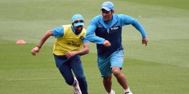 Indian cricket captain Mahendra Singh Dhoni (R) dribbles the ball past teammate Ajinkya Rahane (L) in...