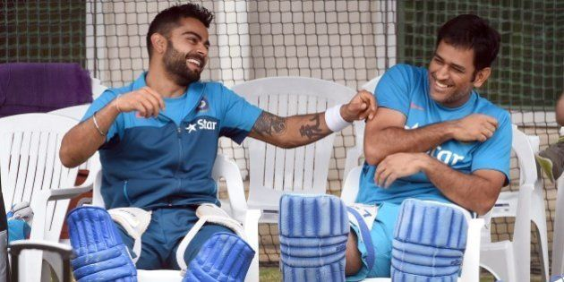 Indian cricket players Virat Kohli (L) and captain Mahendra Singh Dhoni (R) share a lighter moment during...
