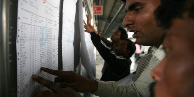 NEW DELHI, INDIA - 2015/02/27: Passengers are checking their name in a train reservation slip at New...
