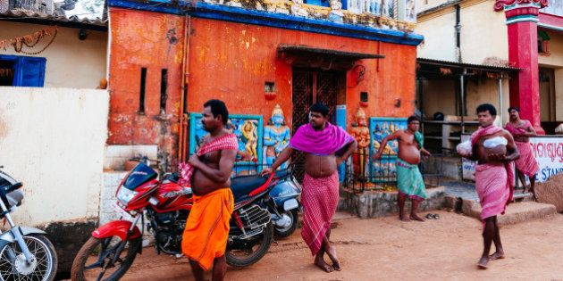 BHUBANESHWAR, ORISSA, INDIA - 2014/01/05: Group of men in lungi in front of a temple. (Photo by Raquel...