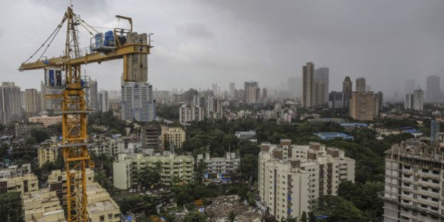 A tower crane operates at a residential construction site, developed by Omkar Realtors & Developers Pvt., in the Parel area of Mumbai, India, on Friday, Aug. 8, 2014. Omkar is playing an important role in Mumbais plan to do something about its enormous and embarrassing problem: at least 6.5 million slum dwellers, still living without running water, private toilets or the basics of sanitation. Omkar's Cresent Bay development consists of six luxury towers with million-dollar apartments overlooking the Arabian Sea, coupled with housing blocks nearby with free homes for all the slum dwellers with rights to the land. Photographer: Dhiraj Singh/Bloomberg via Getty Images