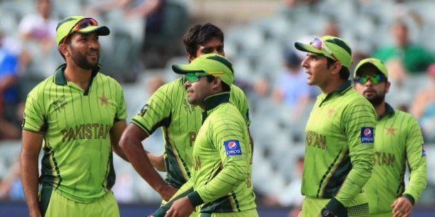 Pakistan's Umar Akmal, center, celebrates with teammates after taking a catch to dismiss Ireland's...