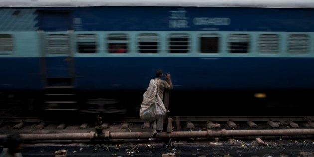 An Indian ragpicker waits for a train to pass by as he tries to cross railway tracks in New Delhi, India,...