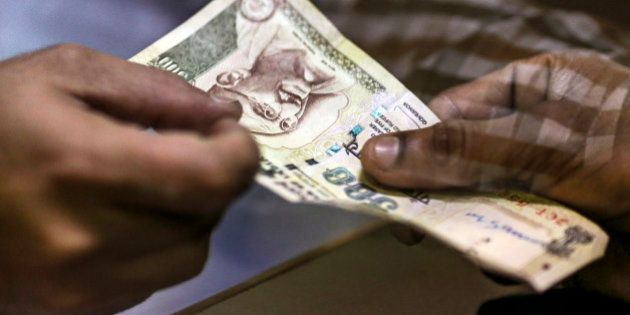 A customer deposits a Indian five-hundred rupee banknotes at a branch of the HDFC Bank Ltd. in Mumbai,...