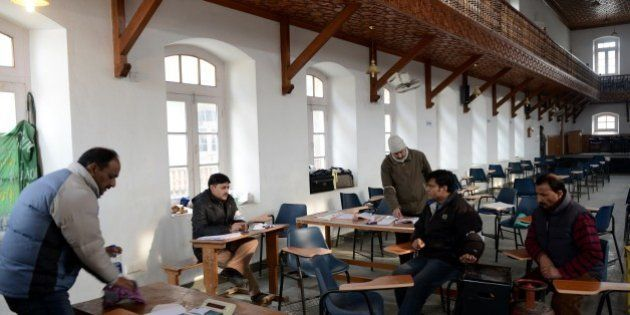 Election commission workers are pictured at a polling station in Srinagar on December 14, 2014. India-administered...