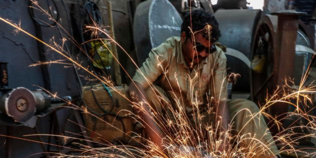 Sparks fly as an employee uses an angle grinder at an Ishwar Engineering Co. factory in Mumbai, Maharashtra,...
