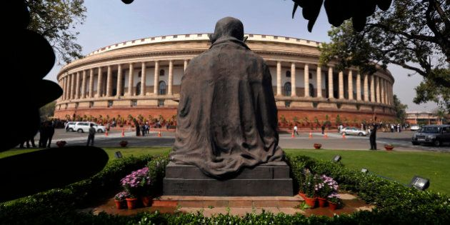 A statue of Mahatma Gandhi overlooks Indian parliament house in New Delhi, India, Saturday, Feb. 28,...