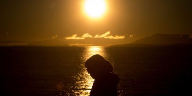 A woman is silhouetted on the deck of the B.C. Ferries vessel Spirit of British Columbia, as the sun...