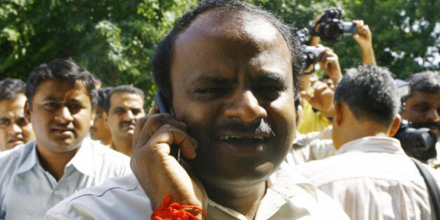 Chief Minister of the Indian state of Karnataka H.D. Kumaraswamy (C) speaks on a cellular telephone while...