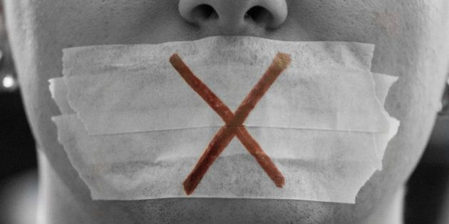 'A male face with a taped mouth and a red cross on it symbolizing censorship.Censorship is all around.Freedom...