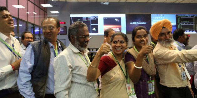 Indian Space Research Organisation scientists and officials cheer as they celebrate the success of Mars...