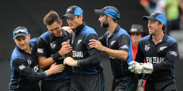 New Zealand's Trent Boult, second left, is congratulated by teammates after dismissing South African...