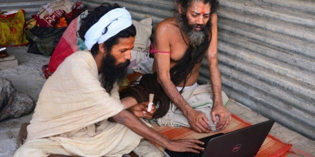 ALLAHABAD, INDIA - 2015/01/04: Sadhus working on laptop in their tent at the bank of Sangam during Magh...