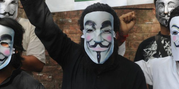 Activists supporting the group Anonymous wear masks as they protest against the Indian Government's increasingly...