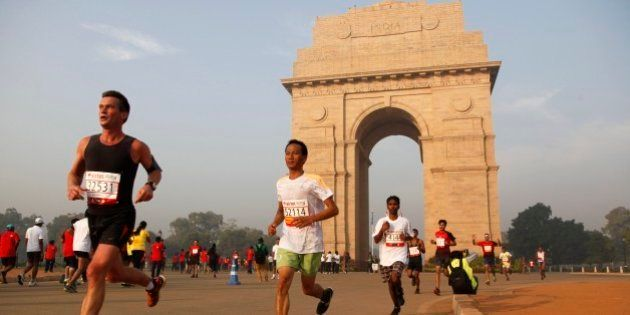 Participants of Delhi Half Marathon run past the India Gate war memorial in New Delhi, India, Sunday,...