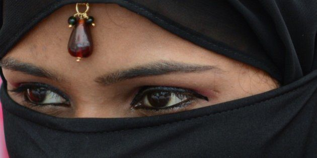 An Indian Muslim bride looks on during a mass wedding ceremony at the ancient Sarkhej Roza mosque and...