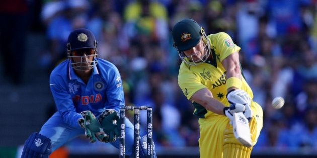 Australia's Shane Watson hits the ball for six runs as India's MS Dhoni watches during their Cricket...
